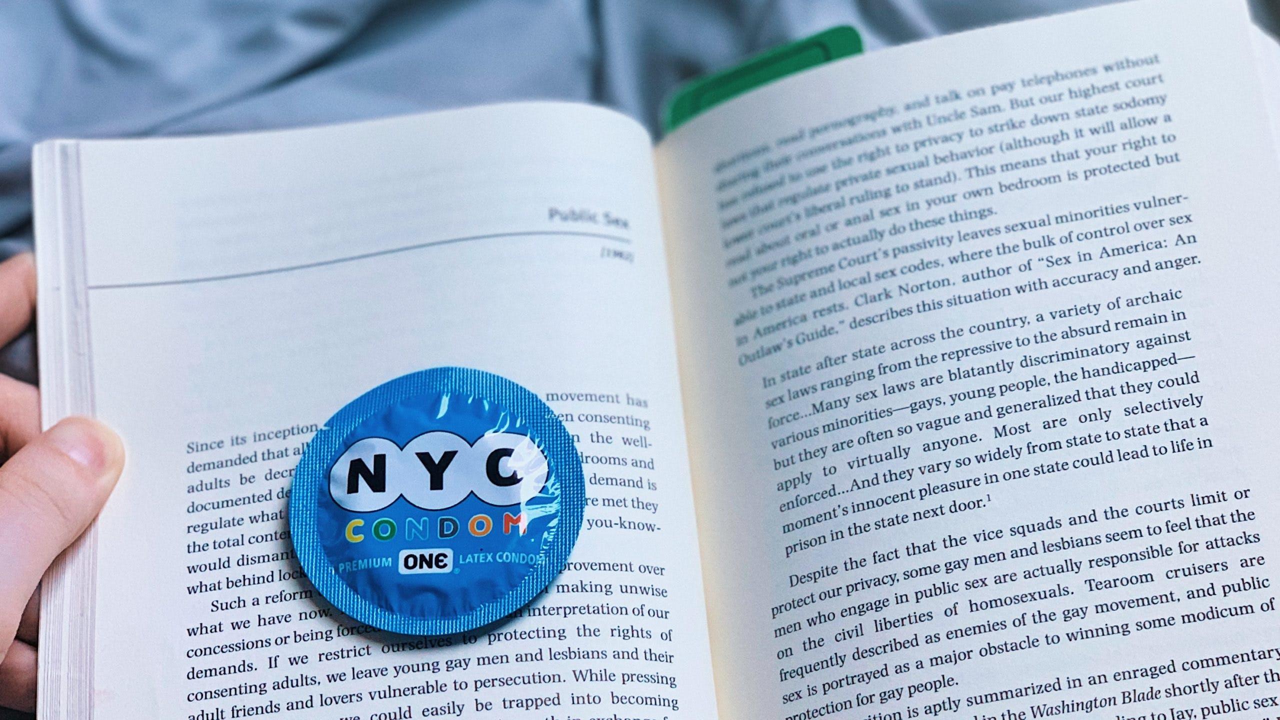 """A closeup of a condom on top of Pat Califia's essay """"Public Sex."""""""