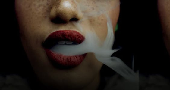 A woman erotically blows smoke from her lips in Bellesa's erotica for women