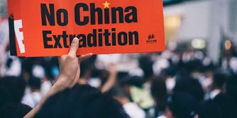 A protesters in Hong Kong holding up a sign