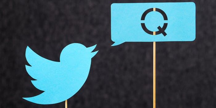 twitter bird on stick with speech bubble that is filled with a cutout Q