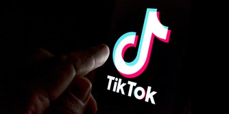 finger reaching out to touch tiktok logo