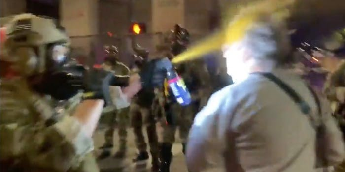 A man being pepper-sprayed in the face by police