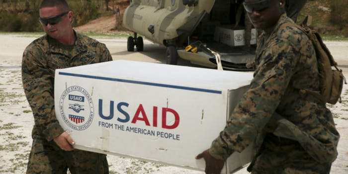 Soldiers holding a box with the USAID