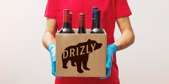 man with gloves delivering wine in a Drizly-branded cardboard box