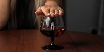 woman covering a glass of alcohol with her hand