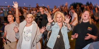 people praying in large crowd without wearing masks during coronavirus pandemic