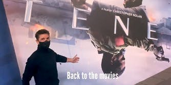 "tom cruise in front of Tenet movie poster with ""Back to the movies"" subtitle"