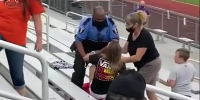 A police officer arresting a woman for not wearing a mask