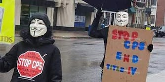 "people wearing guy fawkes masks carrying ""stop cps"" signs"