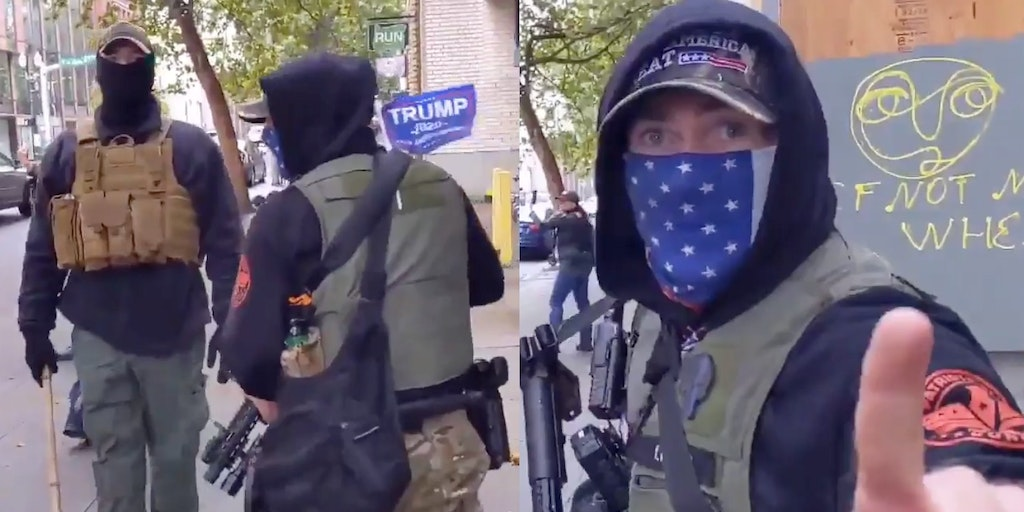 A man in a MAGA hat seen with his assault rifle next to another man with a stick and holding a Trump flag
