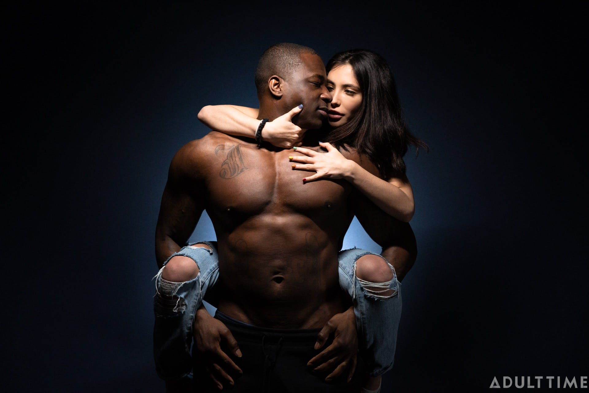An image showing a topless man carrying a woman on his shoulders.