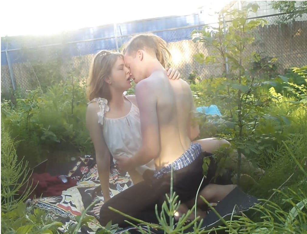 Two people kiss on a picnic blanket in a romantic outdoor scene, surrounded by plants.