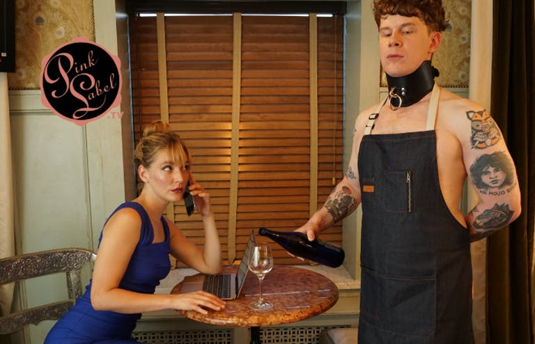 An image showing a woman working on her laptop and phone, while a tattooed man in an apron and large collar pours her a glass of wine.