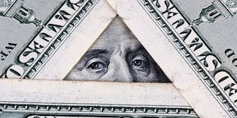hundred dollar bills arranged in a triangle, showing benjamin franklin's eyes