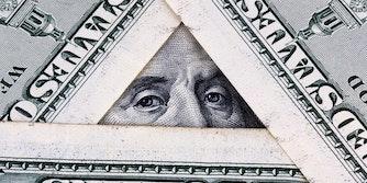 hundred dollar bills arranged in a triangle, showing benjamin franklin's eyes