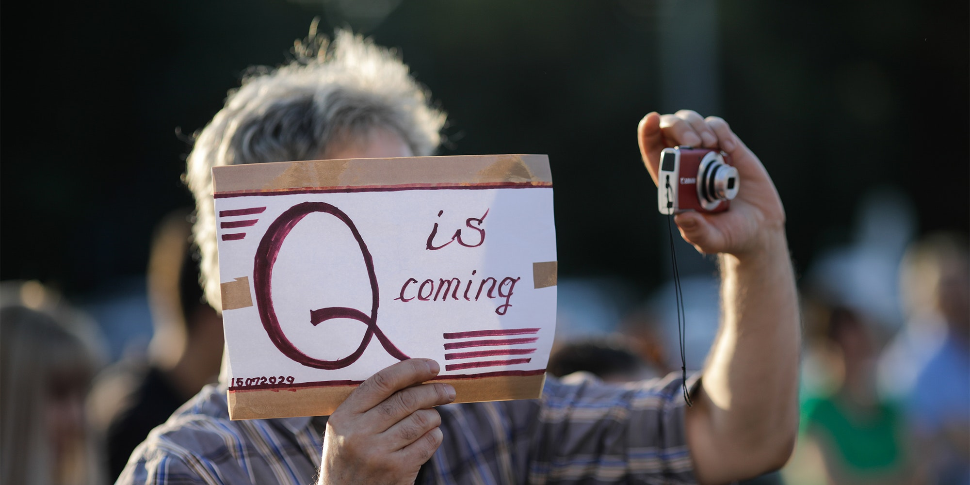 """man holding camera and """"q is coming"""" sign"""