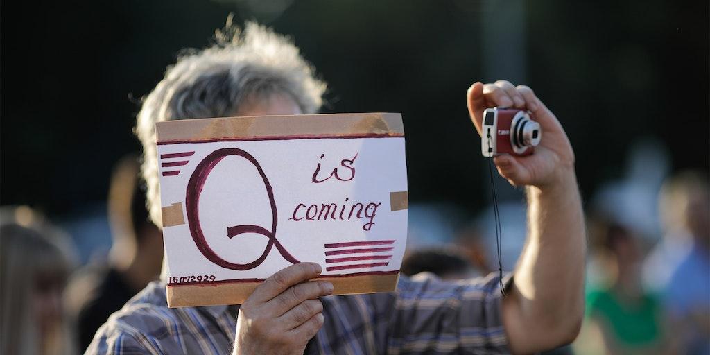 """男人拿着相机,还有""""q来了""""的标志"""