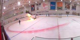 zamboni on fire in the center of a hockey rink