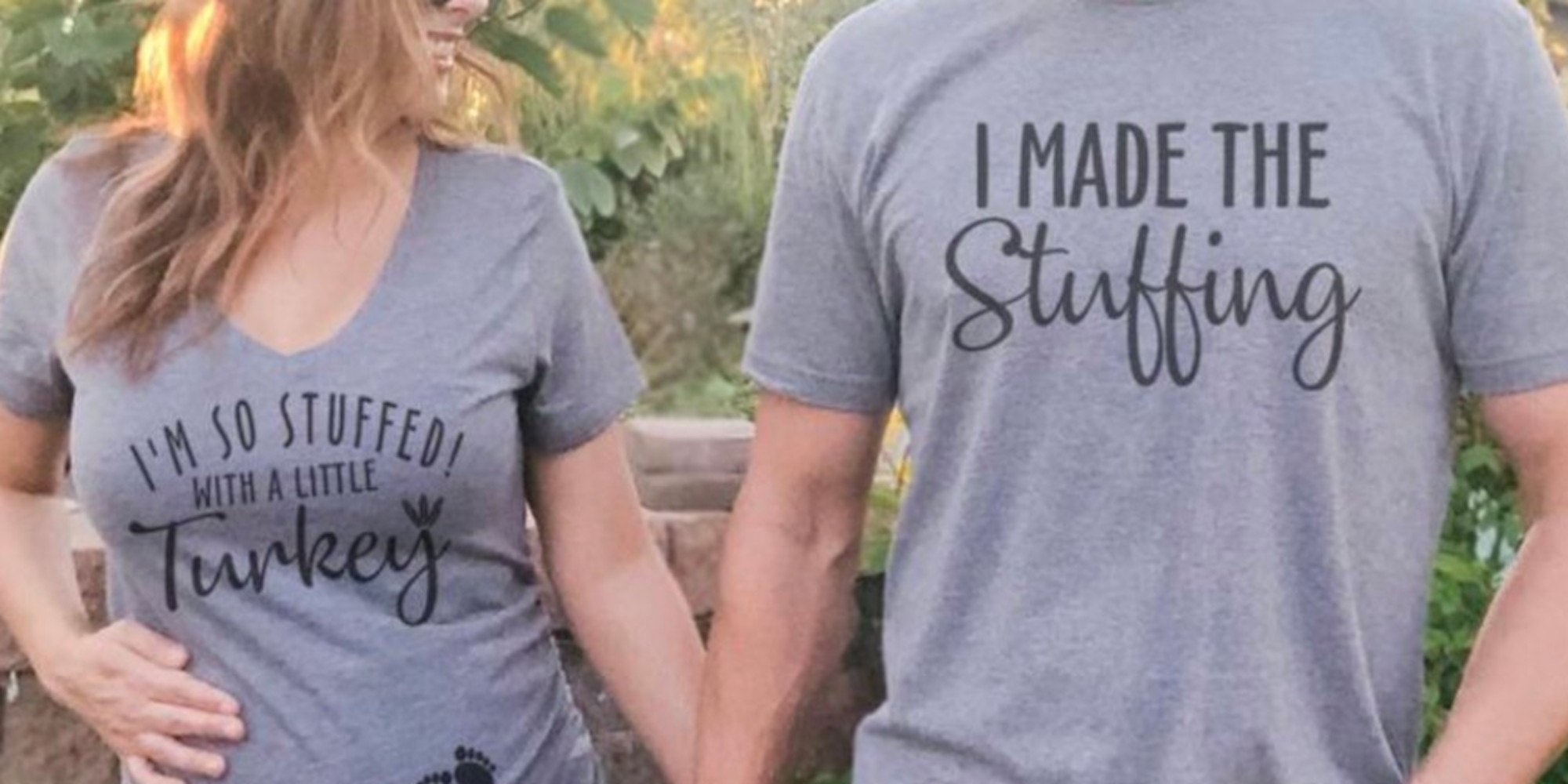 """a white pregnant woman with wavy blonde hair wearing a grey t-shirt saying """"I'm so stuffed with a little turkey"""" and a pair of baby footprints, she's smiling at a man in a matching shirt that says """"I made the stuffing"""""""
