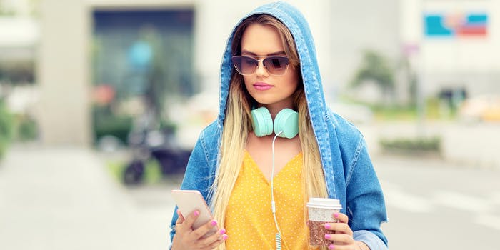 woman in hoody and sunglasses walking with coffee and phone