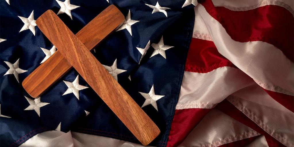 wooden cross on American flag