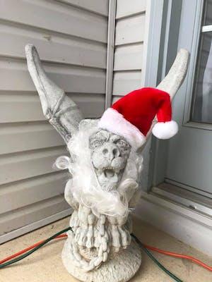 A stone gargoyle wearing a red Santa hat and a false beard