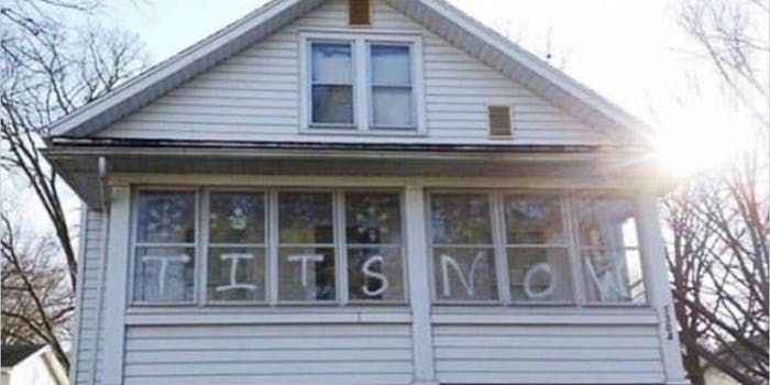 photograph of a house showing tits now written on the windows