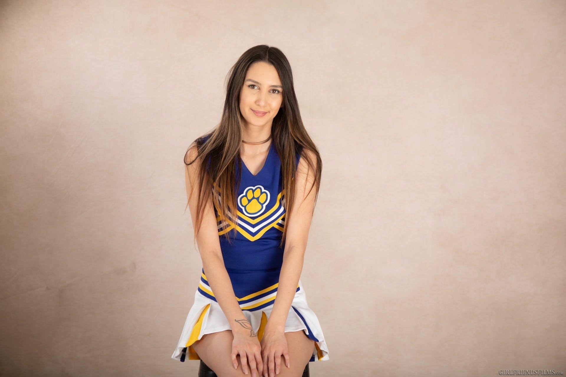 Andreina Deluxe smiling in her cheer uniform.