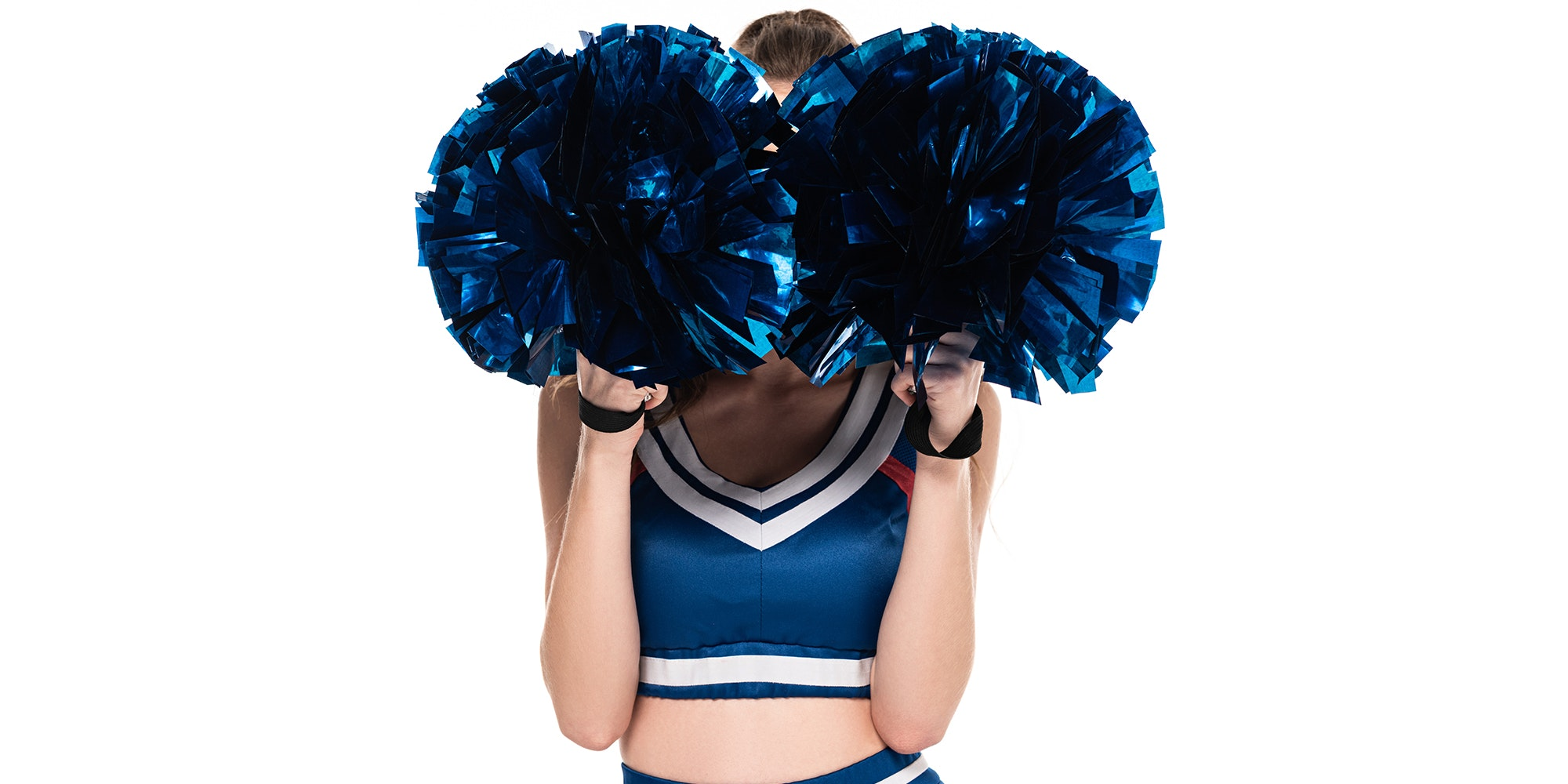 Cheerleader stands with pom poms in her face.