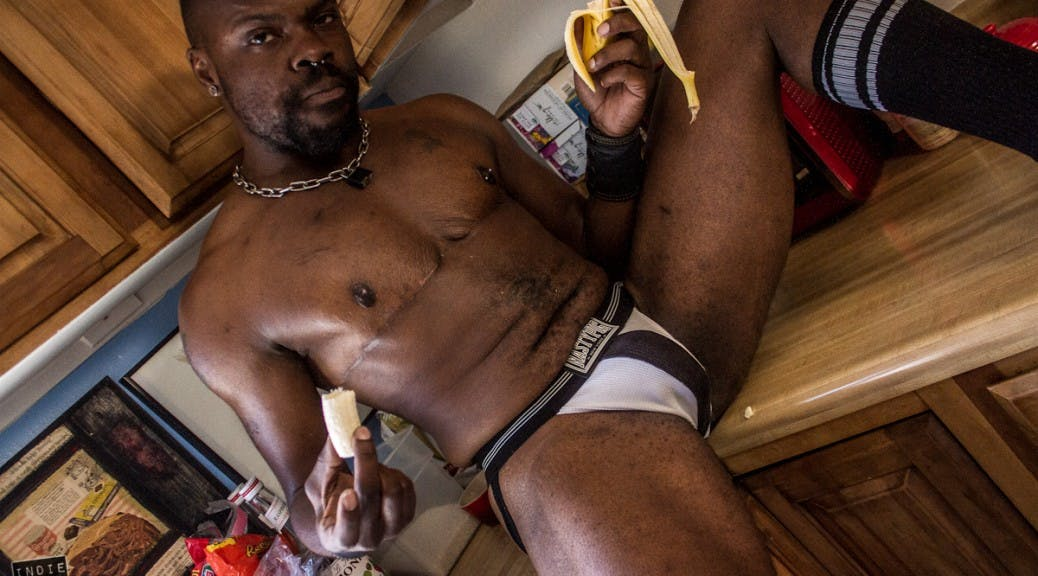 Photo of Rex in nothing but his underwear eating a banana on a kitchen counter.