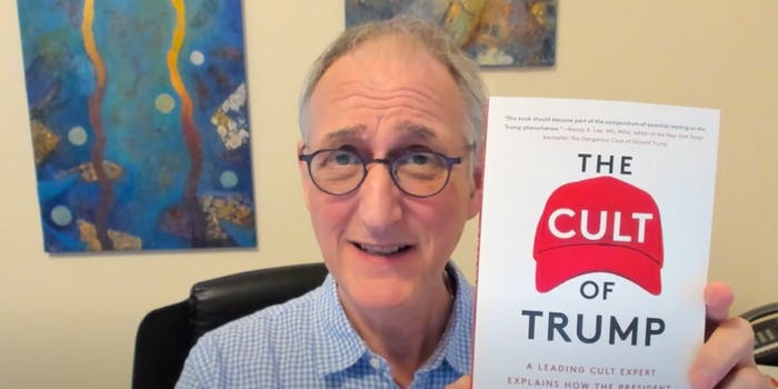 an older white man in black framed glasses makes an awkward, earnest expression while holding up a red and white book called The Cult of Trump
