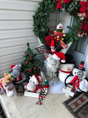 three hippos in Santa clothing, a small Christmas tree with red ornaments, Frank the Gargoyle, two plushie snowmen, an elf on the shelf holding a Die Hard placard and a Christmas hat wearing coronavirus plushie coming out of a wreath