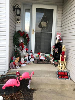 Two pink plastic flamingoes stand in front and to the left of the porch which contains all the decorations described previously. One flamingo wears a red bobble hat and the other one a red scarf.