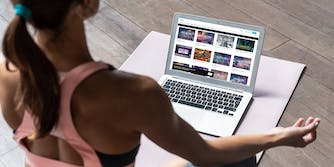 woman in yoga pose watching conspiracy videos on laptop