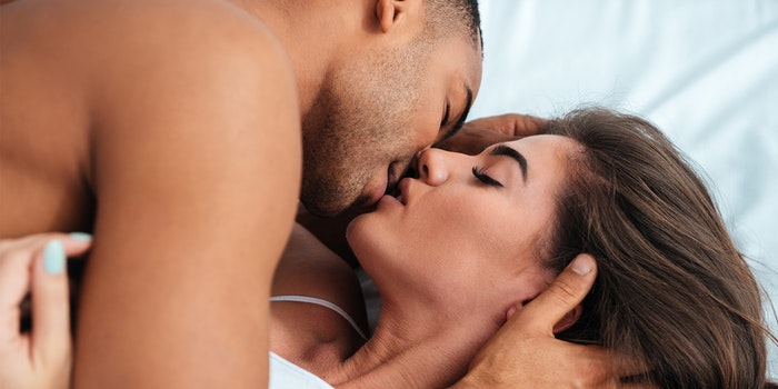 A man kisses a woman in bed.