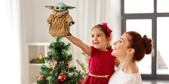 mother holding up little girl to place grogu on top of the christmas tree