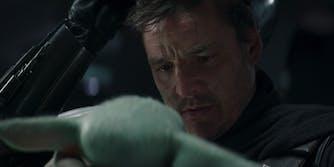 Photo of The Mandalorian taking off his mask to say goodbye to Baby Yoda, aka Grogu.