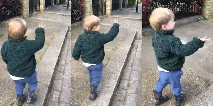 young boy waves hi to pretend strangers on walk