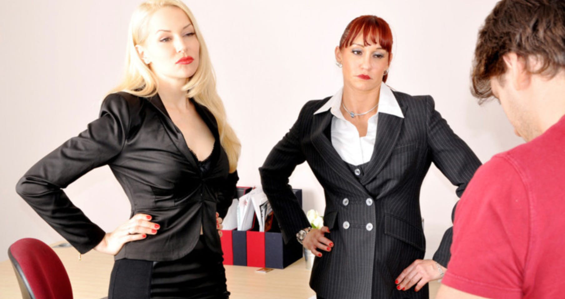 Two women dressed in business attire scowl at a man with their hands on their hips.