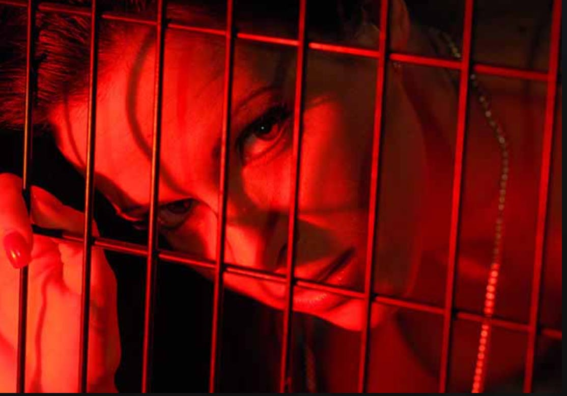 Mature woman seductively stares out of a cage.