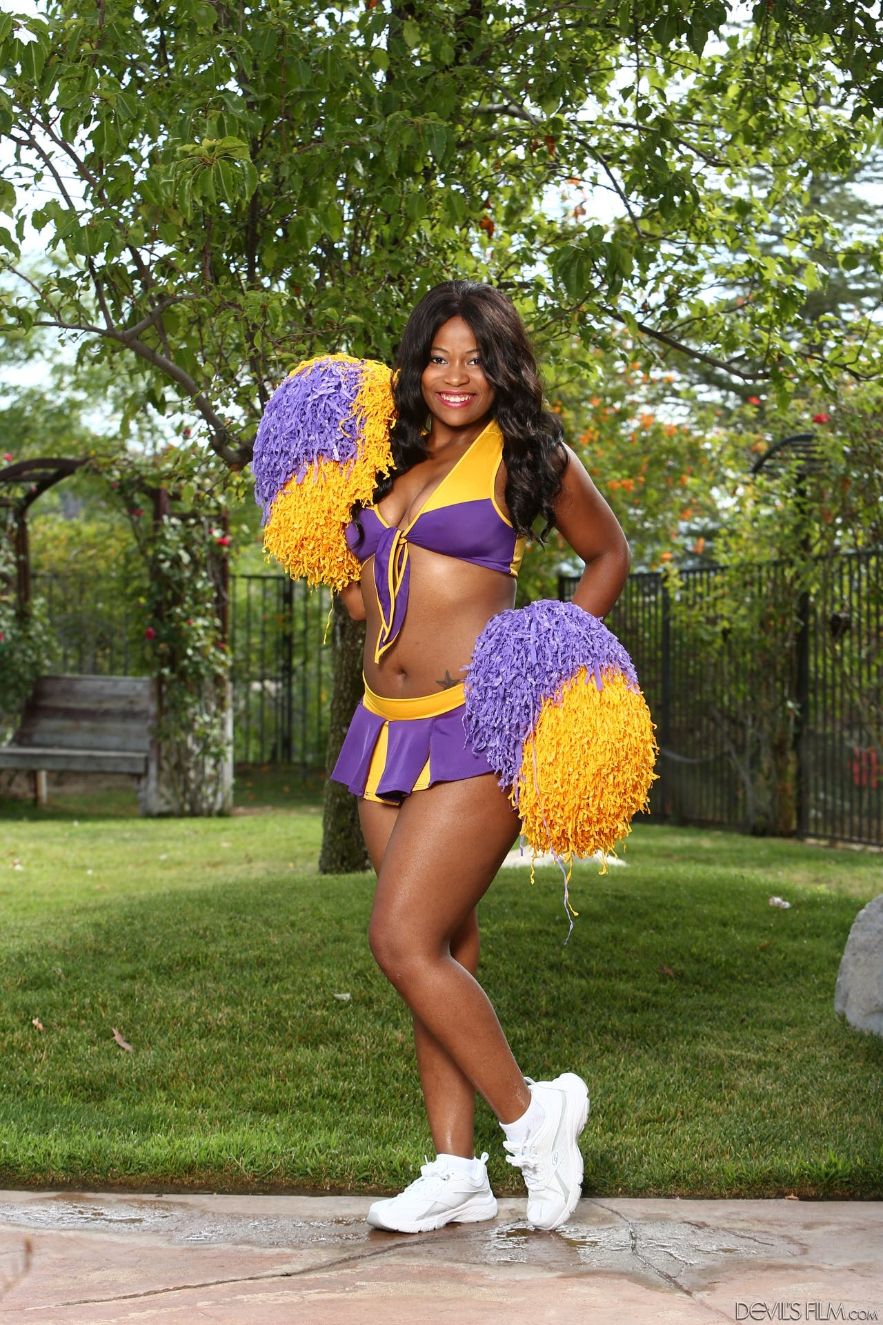 Monique Symone poses outside in her cheerleader uniform.