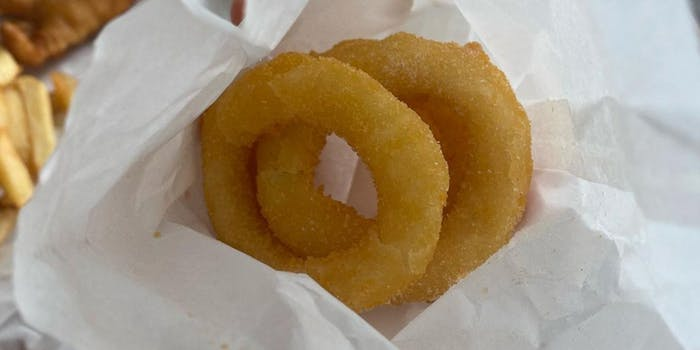 Two pale onion rings laid on crinkled white paper