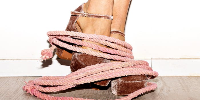 Photo of pink rope around a woman's feet which are wearing suede pumps.