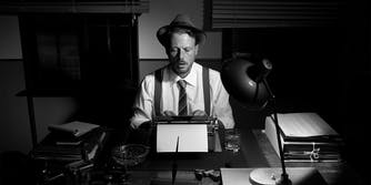 reporter in hat using typewriter
