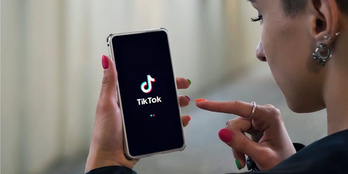 side profile of person with earrings and colorful nails using tiktok