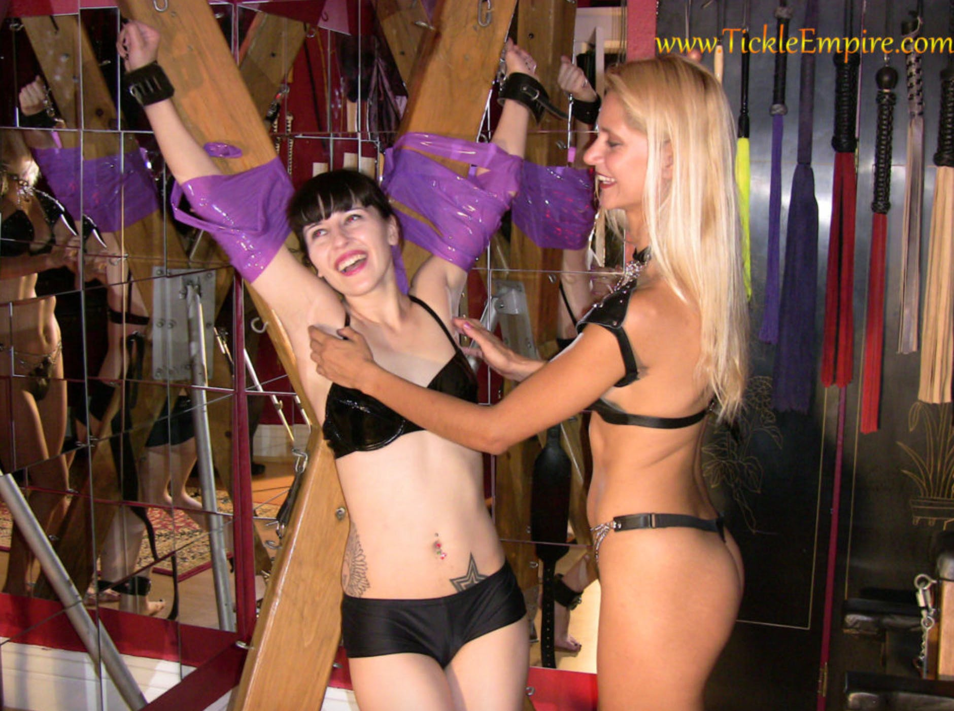 Jezabel is tied to a cross with purple duct tape wearing nothing but a PVC bikini, while Angelie tickles her armpits.