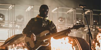 Twenty One Pilots Joseph Tyler, accused of racism after resurfaced tweets, plays guitar wearing a ski mask.