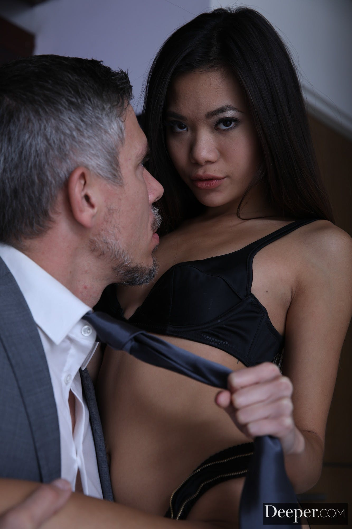 Close up image of Vina Sky pulling Mick Blue's tie and choking him with it.