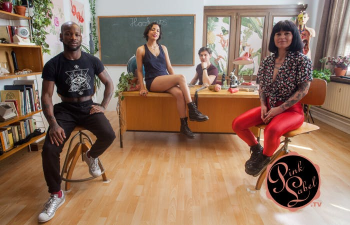 """Image of four adults sitting in a classroom with a chalkboard that has """"hookups"""" written on it behind them."""