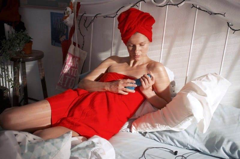 Photo of a woman laying in bed holding a rabbit vibrator with a red towel in her hair and another wrapped around her body.
